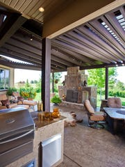 This Loveland outdoor living space includes a grilling station, seating area, and dining table/fire pit.