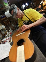 Richard Stutzman, a luthier at Stutzman's Guitar Center, wet sands a repaired crack in a turn-of-the-century Martin parlor guitar in 2009.