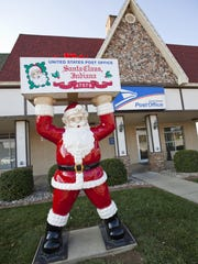 A Santa Claus figure stands in front of the Post Office in Santa Claus, Ind. The name of the town created a major tourist industry.