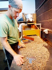 Owen Busse sorts cacao beans at French Broad Chocolates'