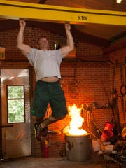 Johnson shows just how strong he is, doing a fingertips-only pull up on a beam at the National Ornamental Metal Museum. Because, if you can, why not?