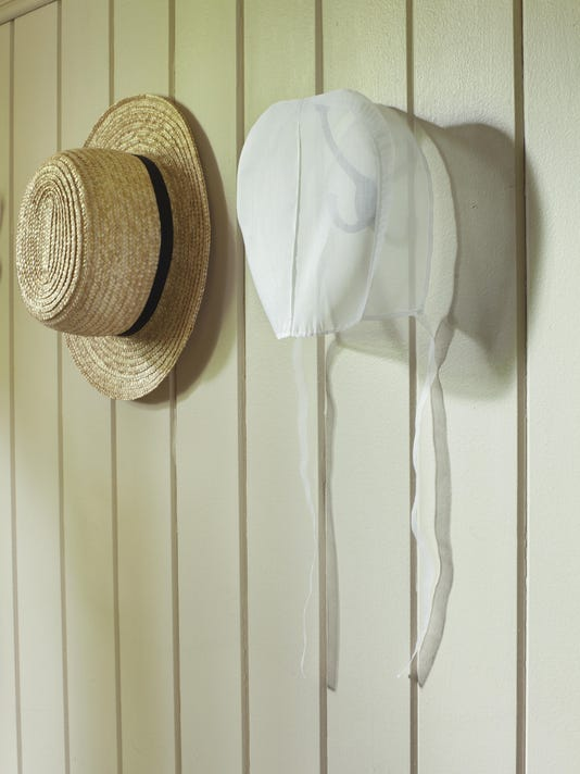 Amish bonnet and straw hat hanging on wall