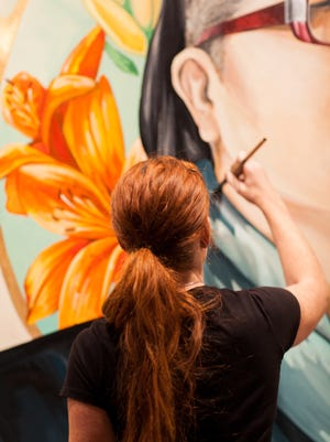 Artist Sarah C. Rutherford works on an image of queer feminist and writer KaeLyn Rich as part of the Her Voice Carries public art project.