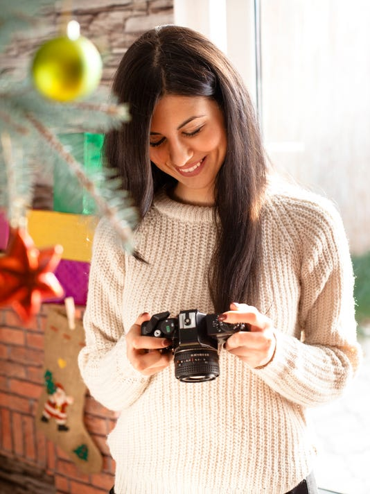 Beautiful smiling girl with old camera