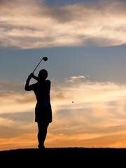 A silhouette of a woman golfer at sunset swinging the golf club.