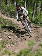 A cyclist makes a run down a trail built by Chad Irey and volunteers. Irey has been busy supervising the construction of natural surface trails in Covington's Devou Park for bikers and hikers since 2009.