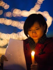 Xi Cao participates in the annual Homeless Memorial Day candle light vigil in Washington Park Friday, December 19, 2014.