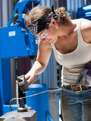 """Carley Eisenberg hammers a heated steel handle for her creation on the HGTV reality show """"Ellen's Design Challenge."""""""