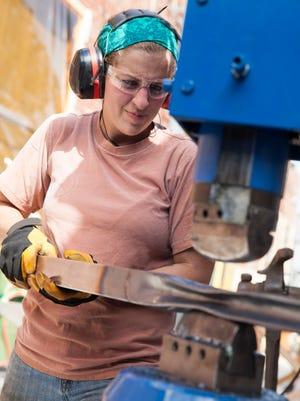 "Carley Eisenberg uses a hydraulic bending machine to compress metal rails for her furniture design on ""Ellen's Design Challenge."""