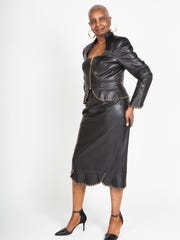Betty Price models a black Karla skirt suit by Ashro. The piece is made with faux leather and features studs with a zip-front jacket and peplum and tulip cuffs.