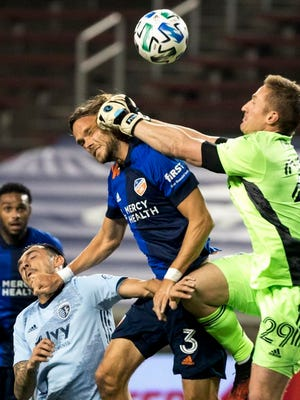 FC Cincinnati defender Tom Pettersson (3) attempts to head a ball as Sporting Kansas City goalkeeper Tim Melia (29) hits him on the head during the first half of an MLS soccer match Wednesday, Oct. 28, 2020, in Cincinnati.