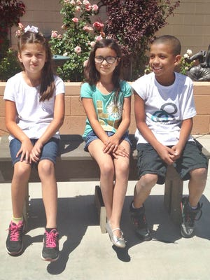 Chandra Cooley, Sofia Rivera, and Giordan Hayes test out a bench made of recycled grocery bags delivered to Mesa's Sirrine Elementary on April 22, 2015.