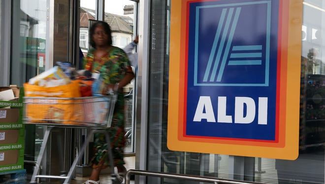 A woman pushes a shoping trolley past an Aldi logo as she leaves one of the company's supermarket stores in London on September 26, 2016.