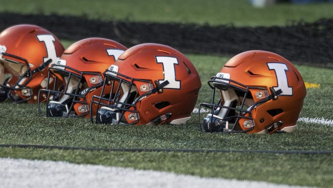 Illinois football helmets sit on the field before a 2017 game against Northwestern.