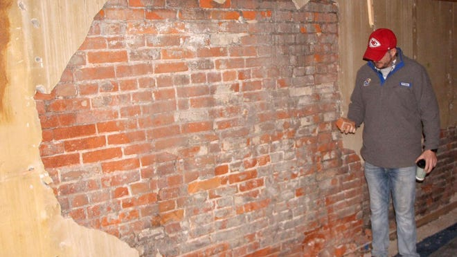 Robert Smiley examines an original brick wall at 317 South Main in Pratt. Smiley has purchased the property that is on the south side of the Barron and is remodeling the building as a rental property.