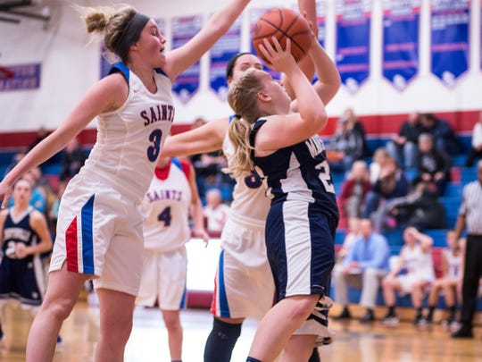 St. Clair's Mia Janssen (#3) and Avery Skonieczny (#34) try to block Marysville High School junior Josie Husson as she shoots the ball during their basketball game at St. Clair High School Dec. 5.