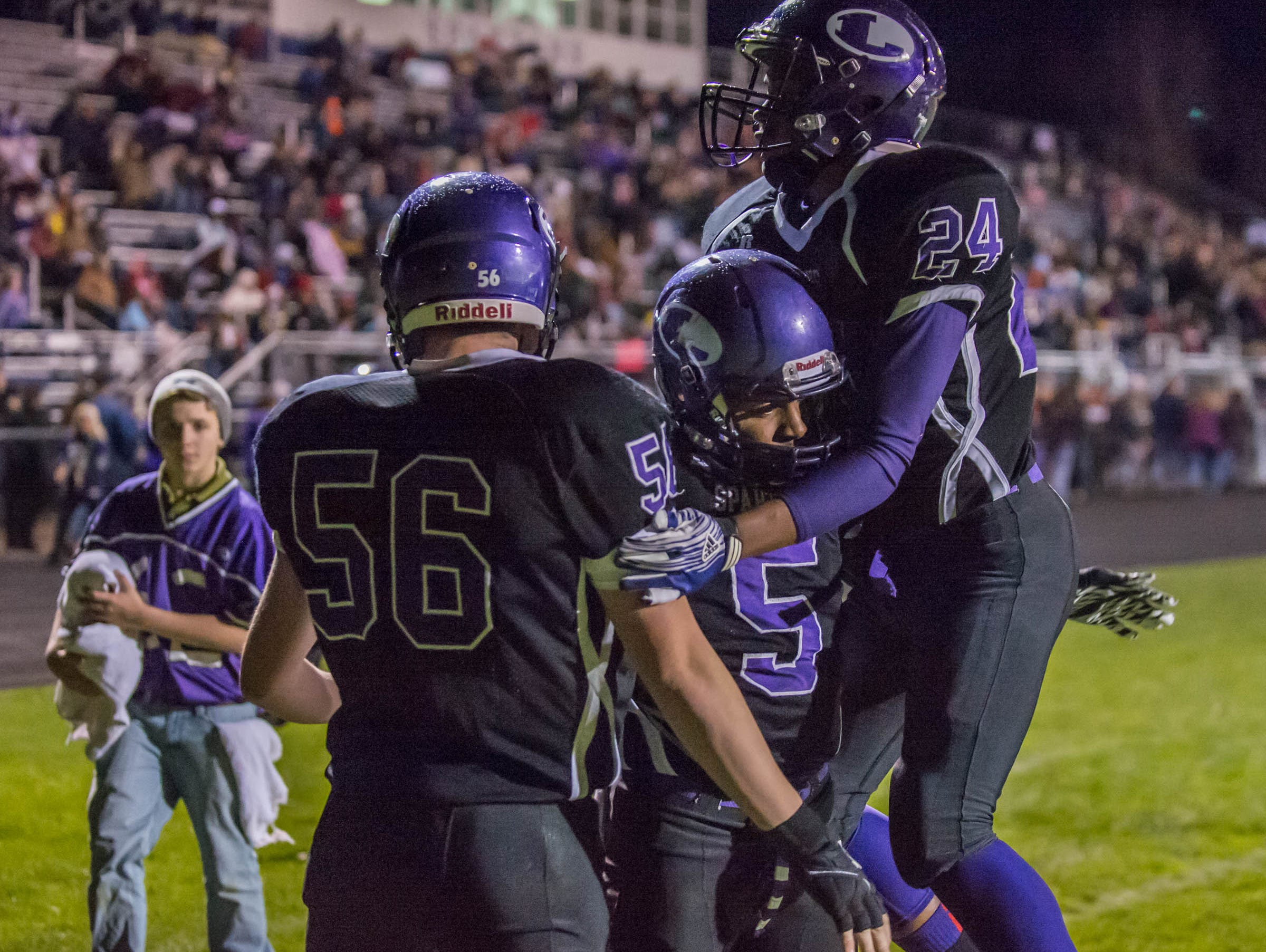 Lakeview's Zach Norstrom (56), Dre' On Kemp (5), and Dashone Asberry (24) celebrate after a touchdown Friday evening against Gull Lake.