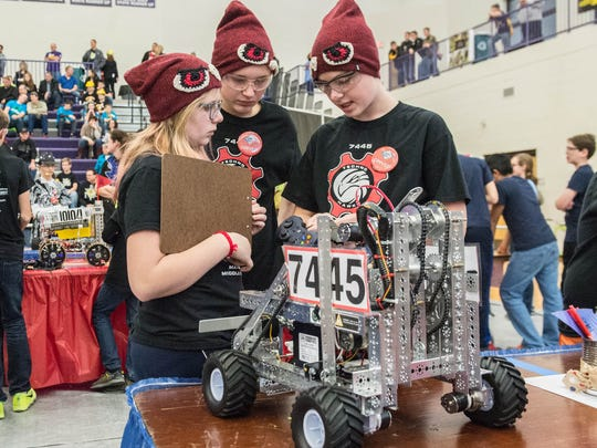Marshall Middle School students Liliana Walker, Grant Doolittle and Logan Dilts check their robot before competing in the FIRST Tech Challenge State Championship at Lakeview High School on Saturday.