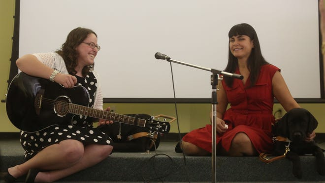Taylor McDonald, at left, performed a song for the audience during a graduation ceremony held at the Guide Dogs of the Desert in Whitewater. McDonald was one of five people who received guide dogs from the center.