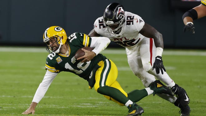 Green Bay Packers quarterback Aaron Rodgers (12) is tackled by Atlanta Falcons' Charles Harris (92) during the second half of an NFL football game, Monday, Oct. 5, 2020, in Green Bay, Wis.