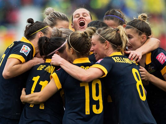 FILE - In this June 21, 2015, file photo, Australia players celebrate after Kyah Simon scored against Brazil during the second half of a FIFA Women's World Cup soccer match in Moncton, New Brunswick. Long before the U.S. women's soccer team filed a federal complaint over wage discrimination, the Australian women fought for better pay. And won.  (Andrew Vaughan/The Canadian Press via AP, File)