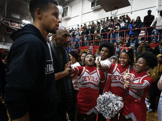 Germantown High School cheerleader Kirasten Phifer (middle) is overcome with emotion after touching the hand of NBA all-star and Golden State Warriors guard Stephen Curry (left) after the jersey retirement ceremony for Ian Clark Friday night.