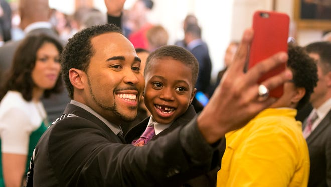 David Johns, executive director for the White House Initiative on Educational Excellence for African Americans, takes a photograph Feb. 26, 2015, with Malik Leak, 6, while waiting for the arrival of President Barack Obama and first lady Michelle Obama during a reception in recognition of African American History Month in the East Room of the White House, Washington, D.C.