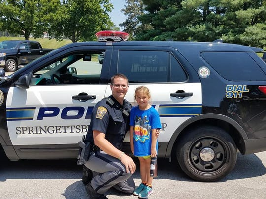 6-year-old Marie Pittman poses with Officer Cory Landis in front of his police vehicle Saturday afternoon at Springettsbury Township Park.
