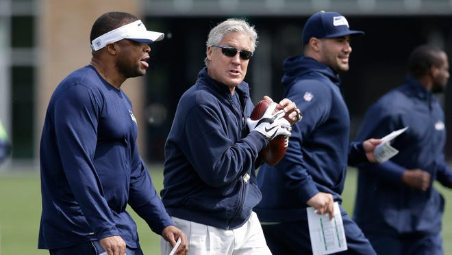 Seattle Seahawks head coach Pete Carroll holds a football as he walks with other coaches during an NFL football rookie minicamp Sunday, May 10, 2015, in Renton, Wash.