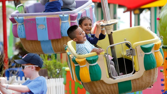 Rubi Sanchez, 5, of Queens and her brother Michael, 4, enjoy a ride on Up, Up and Away at Playland, on opening day, May 10, 2014 in Rye.