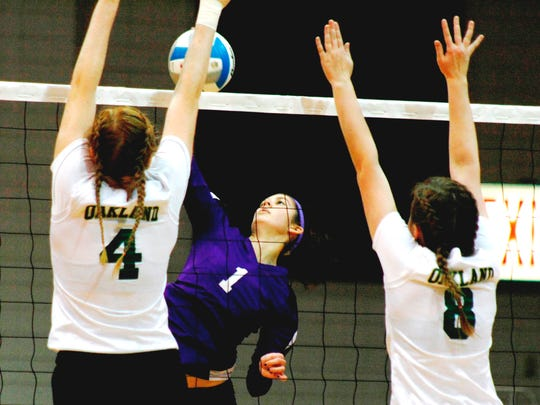 PCA's Olivia Mady (middle) hits through the block of Oakland Christian's Starr Summner (4) and Jacqueline Schneider (8).