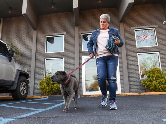 Bo Greene of Greer walks her dog Luna out of The Community Tap in Greenville on Friday.