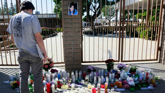 A student pays his respects at a memorial for El Dorado High School teacher Jillian Jacobson, Tuesday, at the school in Fullerton, Calif.