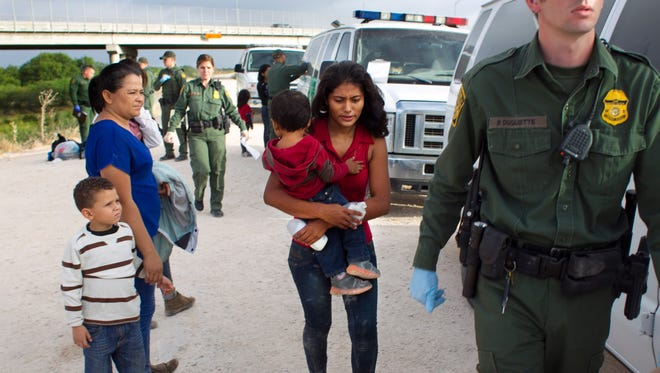 Some of a dozen women and children from Honduras are apprehended by Border Patrol near the Anzalduas International Bridge not far from the border with Mexico at the Rio Grande river in Mission, Tex., on Saturday, June 21, 2014.