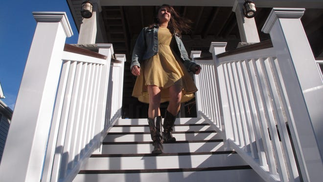 In this Oct. 22, 2015 photo, Krista Sperber walks down the staircase of her newly rebuilt home in Belmar, N.J., shortly before the third anniversary of Superstorm Sandy. Belmar started a fundraising drive that brought in around $240,000 in cash and materials for Sperber and another woman whose home was wrecked in the 2012 storm to finally move back home.