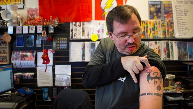 Craig DeMeyers, owner of Two Kings Comics in Victor, shows off his Flash tattoo to a customer on Oct. 16, 2015.