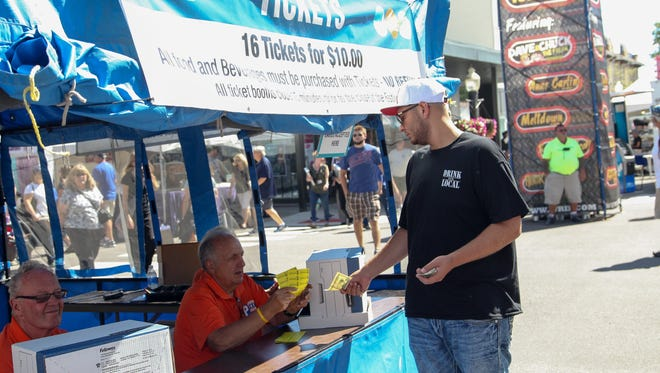 Guests purchase tickets redeemable for food and beverages during opening day of the Arts, Beats & Eats festival in Royal Oak on Friday, September 2, 2016.