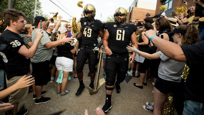 Vanderbilt defensive end Jonathan Wynn (49) and guard Bruno Reagan (61) head to the stadium before an NCAA football game between Vanderbilt and Kansas State at Vanderbilt Stadium in Nashville, Tenn., Saturday, Sept. 16, 2017.