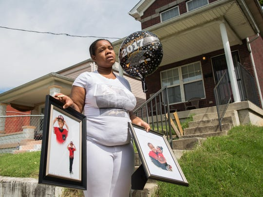 Micheshia Norment holds photos of her son, Dequante Hobbs Jr., 7, who was shot Sunday night by a stray bullet through the window while he was eating a snack at the dinner table. He was supposed to graduate kindergarten on Tuesday. Police are still searching for information on his death. May 22, 2017.