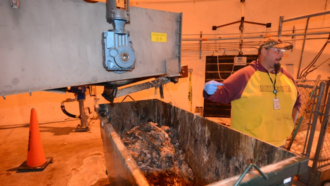 NEW Water treatment plant operator Aaron Eichorst stands next to a bin containing hundreds of wipes flushed into the sewage treatment system and removed by a bar screen at the Quincy Street facility.