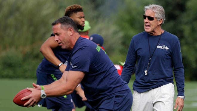 Seattle Seahawks head coach Pete Carroll, right, watches as tight ends coach Pat McPherson, left, tosses the football to players, Thursday, Aug. 13, 2015, during NFL football training camp in Renton, Wash. The Seahawks will play the Denver Broncos Friday in a preseason game in Seattle.