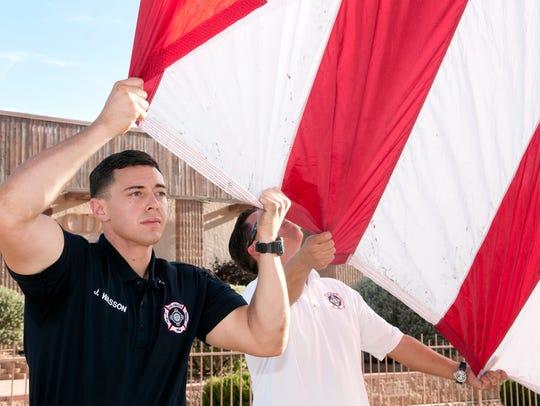 Las Cruces fireman J. Wasson holds the garrison flag
