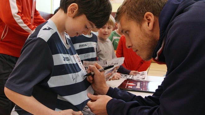 In the spring of 2016, a third-grade class at the Henry Barnard School wrote letters to the soccer stars of the New England Revolution, asking them to come visit the class. Two Revolution players obliged. Here, forward Scott Caldwell signs the shirt of student Holden Langlois.