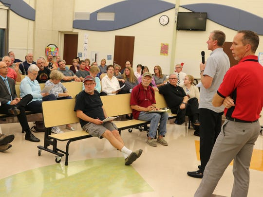 Michael Fite, of F2 Companies, and Pat Adkins, superintendent of Port Clinton City Schools, discuss the possibility of a future athletic conference and other developments during a recent community meeting.