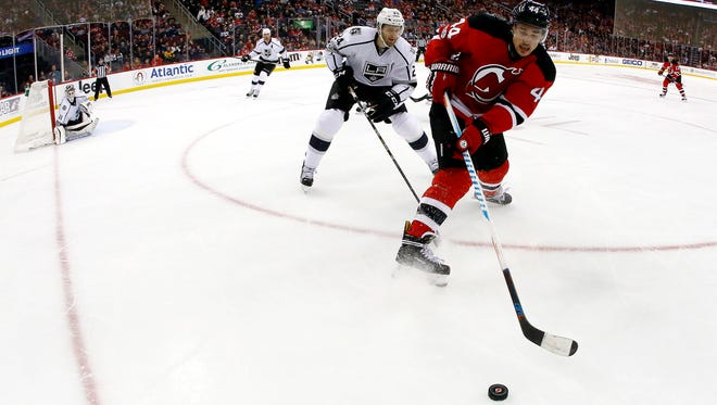 Devils left wing Miles Wood (44) and Los Angeles Kings defenseman Derek Forbort (24) compete for the puck during the second period of a game Tuesday, Jan. 24, 2017, in Newark. The Kings won, 3-1.