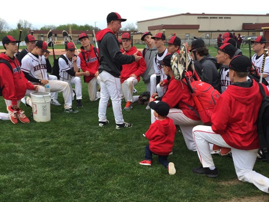 Wapahani coach Brian Dudley talks to the team after a game while two-year-old superfan Bo looks on.