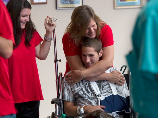 Chelsea Gill, left, smiles Wednesday while Danita Lovins hugs son, Zachary Latawiec, who is recovering from a lightning strike at Golisano Children's Hospital in Fort Myers.