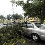 A car is covered by large tree branches in the parking lot of the Licking Memorial Hospital after a strong storm tore through Licking County June 29, 2012, bringing down trees and power lines, damaging homes and snarling traffic.