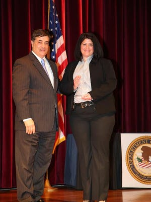 Sgt. Katrina Henderson, right, accepts an award with U.S. Attorney David Rivera of the Department of Justice.