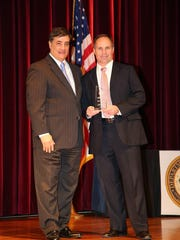 Eric Howser, right, accepts an award with U.S. Attorney David Rivera of the Department of Justice.